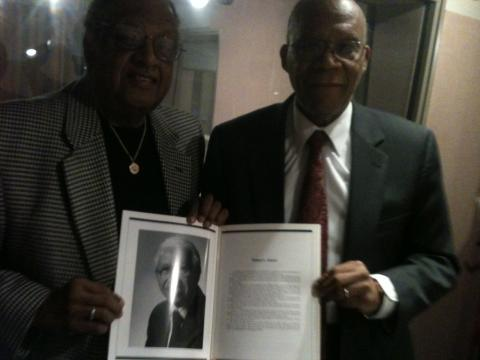 "Ackneil Muldrow II, left, and Larry Gibson hold up a picture of ""Little Willie"" Adams in a program from a Baltimore Marketing Association event honoring him. Poorly lit iPhone photo credit: Lawrence Lanahan."